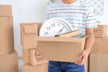 Young man holding moving box in room