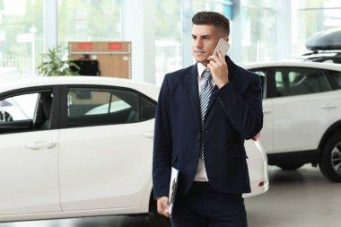 Salesman talking on mobile phone in car salon