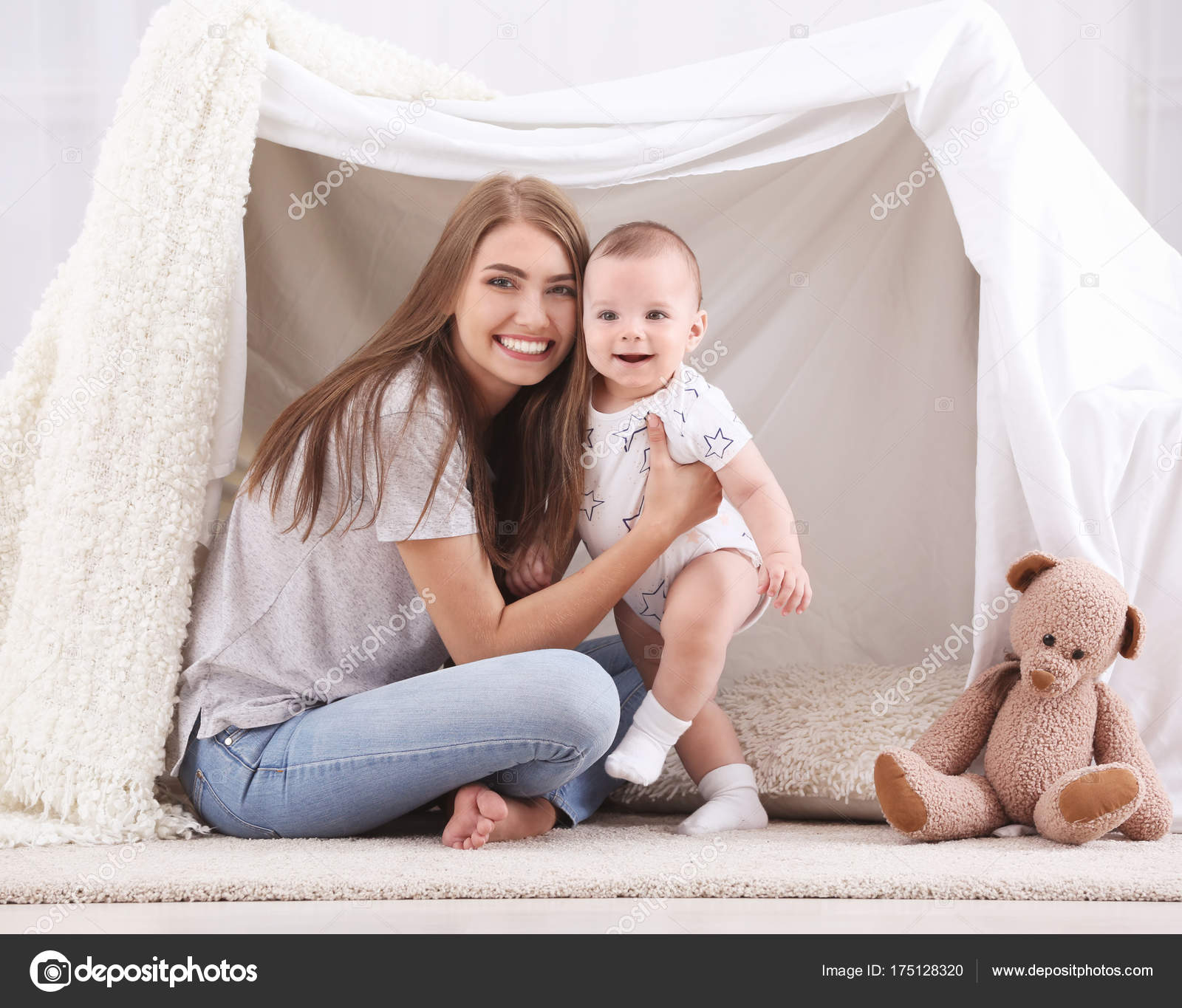Young mother and cute baby playing in tent at home stock photo