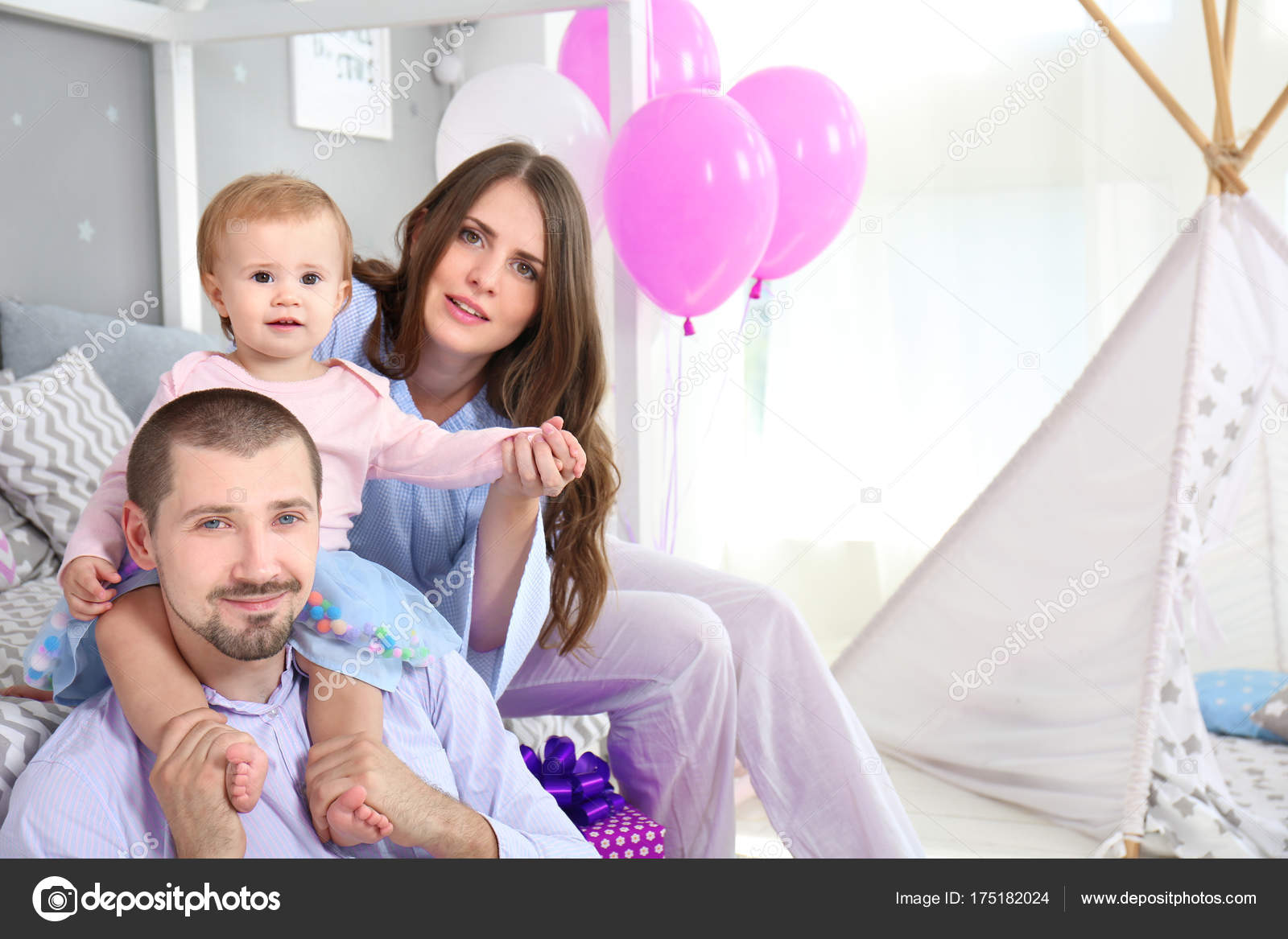 Young family and cute baby celebrating birthday at home stock photo