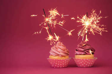 Two tasty cupcakes with sparklers on color background