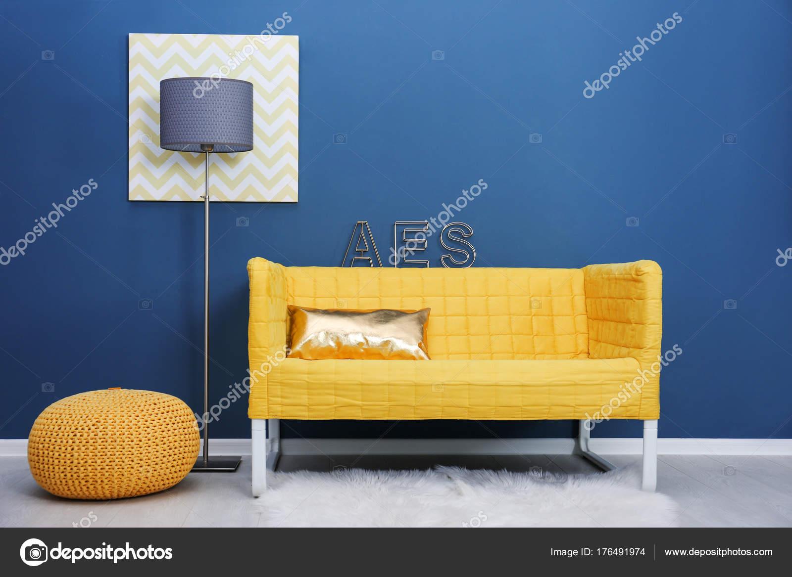 Stylish yellow sofa on color wall background — Stock Photo ...
