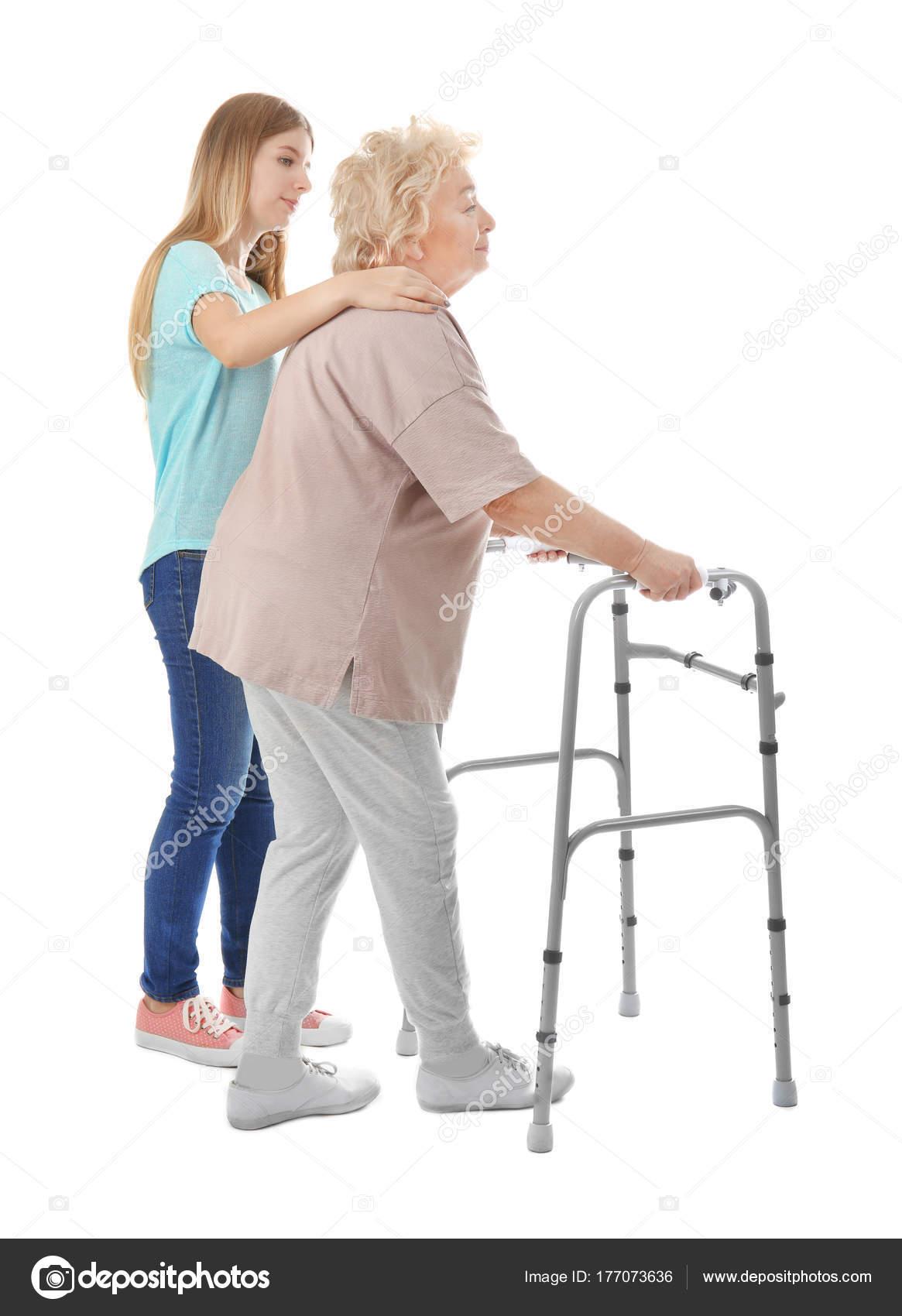 Jonge vrouw en haar bejaarde oma met frame lopen op witte ...