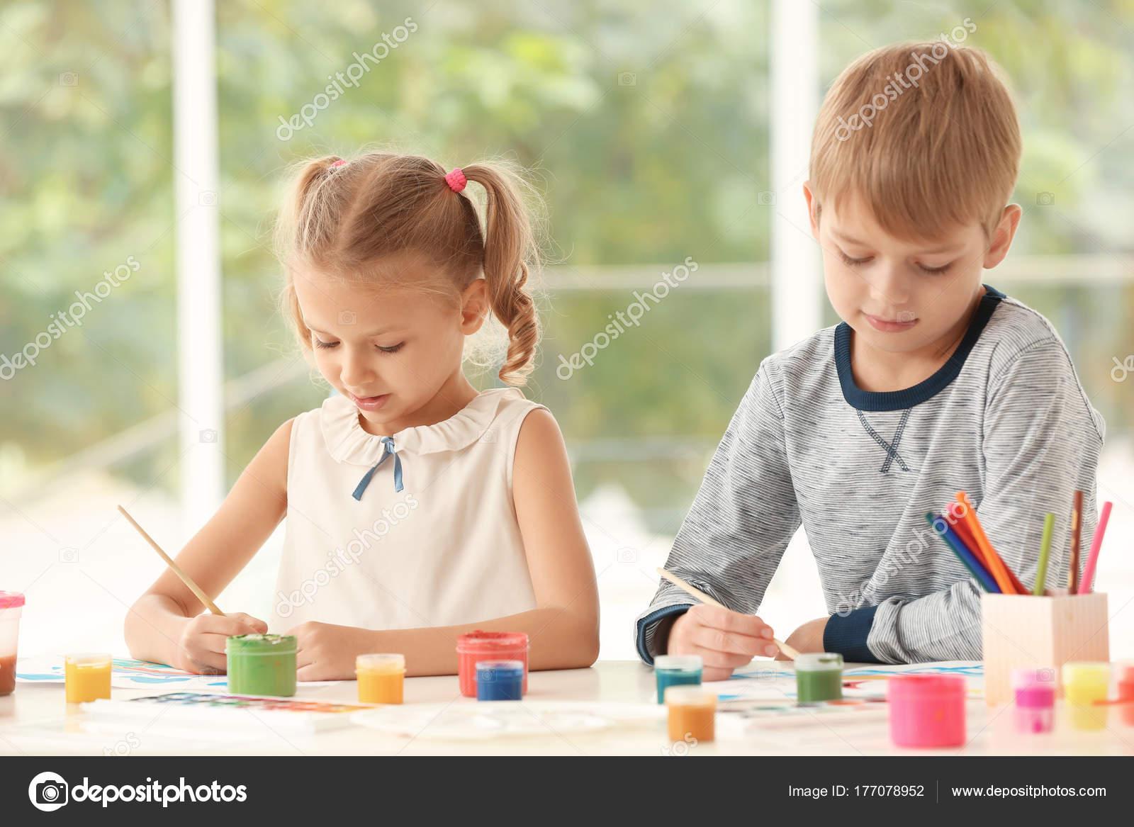 Lindos niños pintando cuadros en la mesa en el interior — Fotos de ...