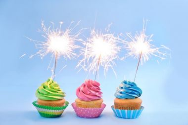 Delicious cupcakes with sparklers on light background