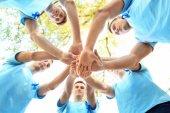 Mladí muži v tričkách s modré stužky stojící v kruhu a drží ruce spolu venku. Koncept povědomí o rakovině prostaty