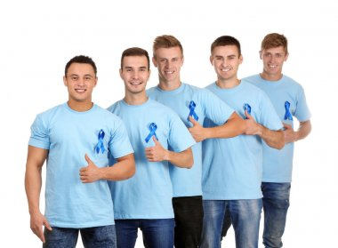 Young men in t-shirts with blue ribbons showing thumb-up gesture on white background. Prostate cancer awareness concept