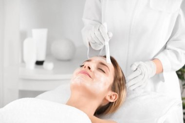 Beautician applying cream on young woman's face in spa salon
