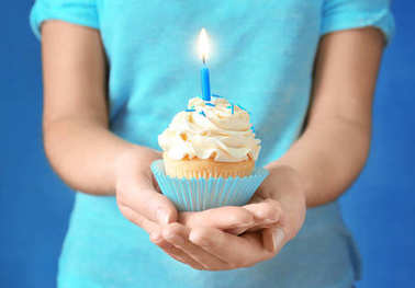 Woman holding cupcake with candle, close up