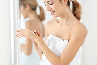 Young woman applying body cream