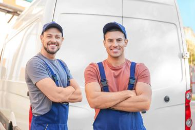 Delivery men standing near car