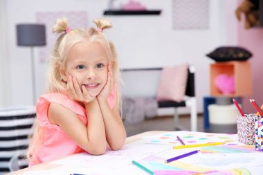 Cute little girl posing with pencil drawings at home