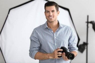 Young photographer with camera in professional studio