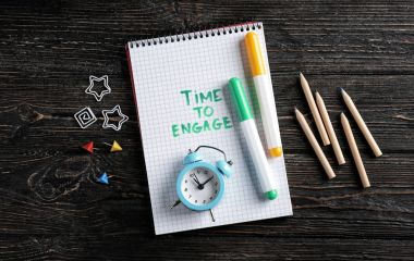 Notebook with written phrase TIME TO ENGAGE, clock and markers on wooden background