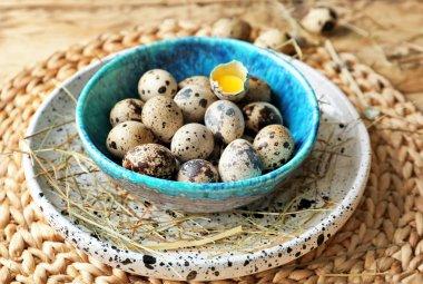 Raw quail eggs in bowl on wicker mat