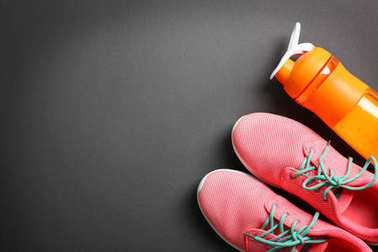 Sneakers with bottle and blank space for  gym exercise plan on black background. Flat lay composition