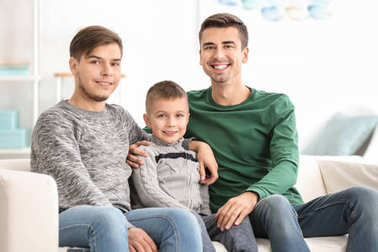 Male gay couple with adopted boy sitting on sofa at home