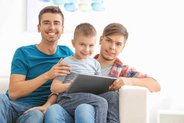 Male gay couple and adopted boy with tablet at home