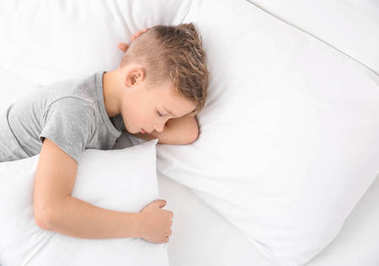 Cute boy sleeping on white pillow at home