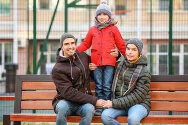 Male gay couple with adopted boy sitting on bench in park