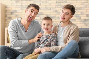 Funny male gay couple with adopted boy on sofa at home
