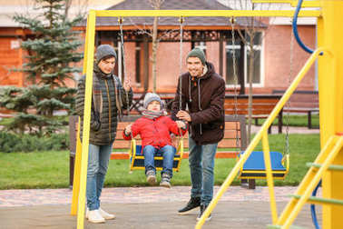 Male gay couple with adopted boy at playground