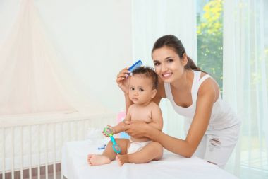 Mother combing cute baby after bathing at home