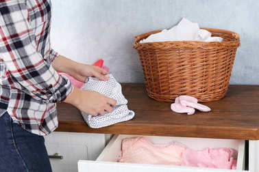 Woman folding laundry on table, indoors
