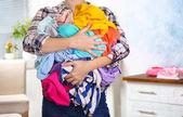 Frau hält Haufen von schmutzigen Wäsche, drinnen