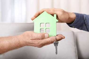 Real estate agent with senior man holding house model and key indoors
