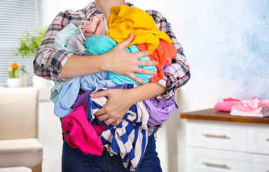 Woman holding pile of dirty laundry, indoors