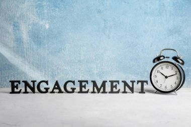 Word ENGAGEMENT and clock on table