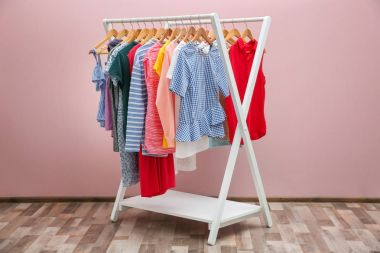 Rack with different clothes near color wall