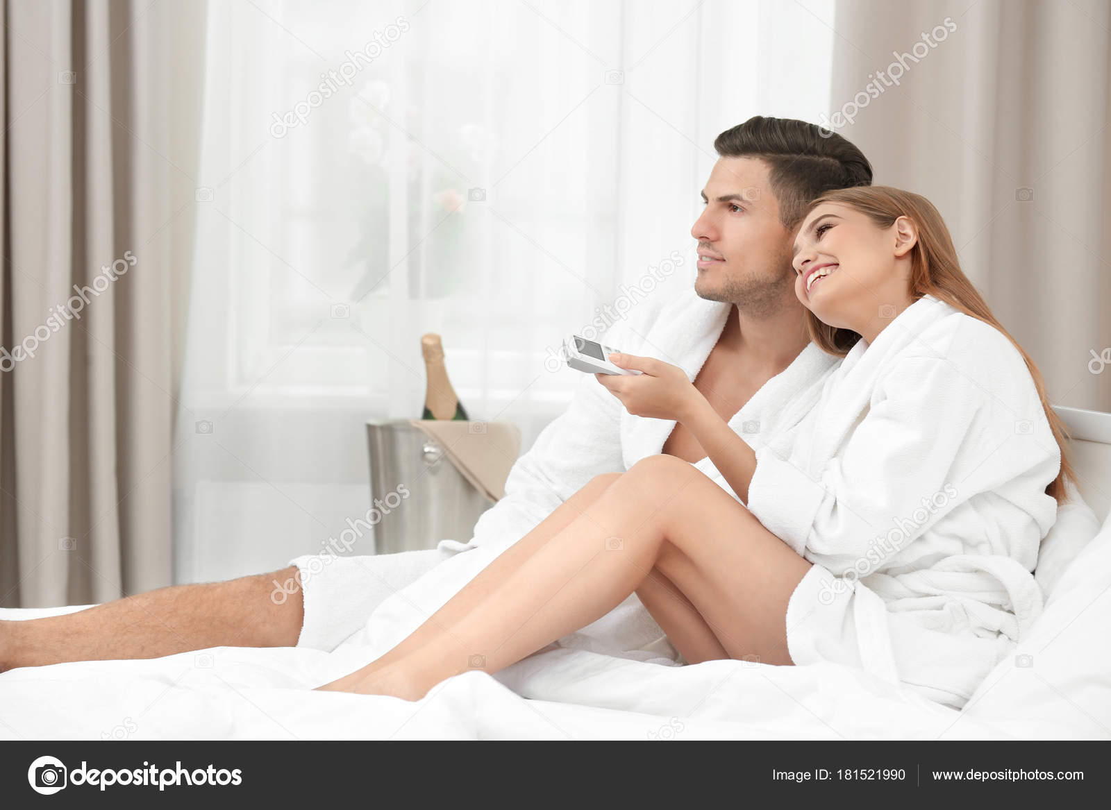Young loving couple in bathrobes relaxing on bed at hotel — Stock Photo 7d8331414