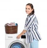 Nő a kosár közelében mosógép fehér háttér