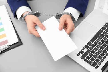 Businessman in handcuffs holding envelope with bribe at table, closeup