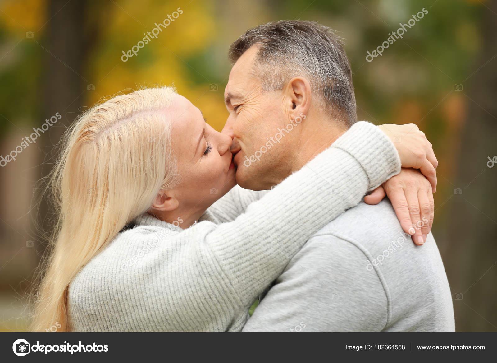 happy mature couple kissing outdoors — stock photo © belchonock