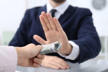 Businessman refusing to take bribe indoors, closeup
