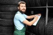 Fotografie Mužské mechanik s schránky u pneumatiky v automobilu uchovávat