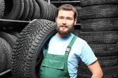 Fotografie Mužské mechanik s auto pneumatiky v automobilovém obchodě