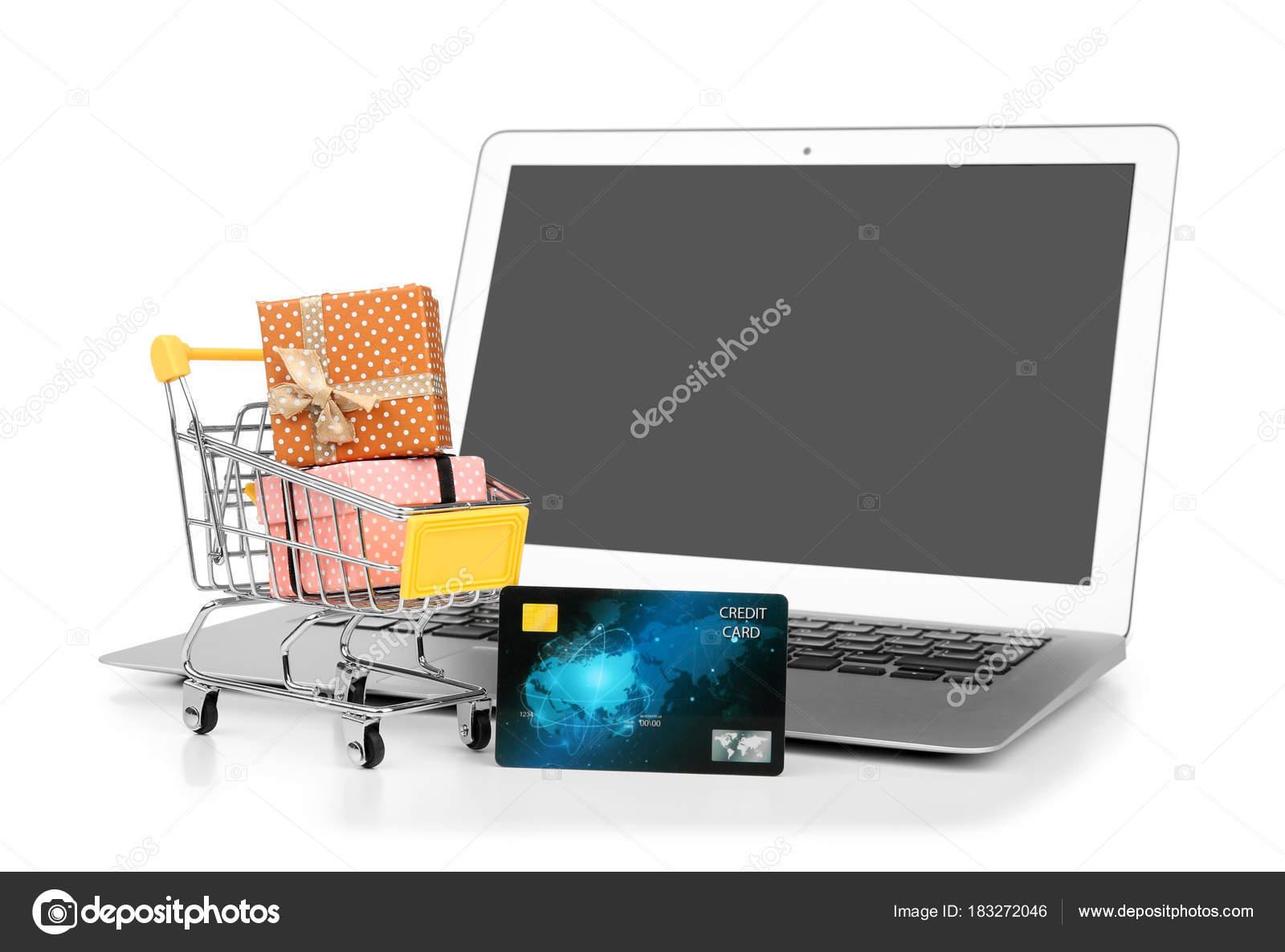 710b8eefd72257 Computer portatile, carta di credito e piccolo carrello con scatole regalo  su priorità bassa bianca. Concetto di acquisto del Internet– immagine stock