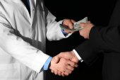 Doctor receiving bribe from businessman on black background, closeup