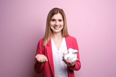 Young woman with broken piggy bank and coins on color background
