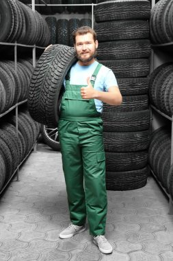 Male mechanic with car tire in automobile store
