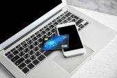 Mobilní telefon a kreditní kartou na klávesnici pro laptop, closeup. Internetové nákupní koncept
