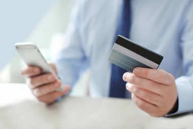 Man with credit card and mobile phone, indoors