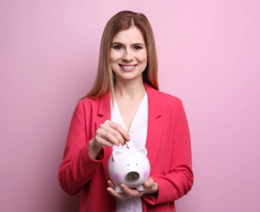 Young woman putting coin into piggy bank on color background