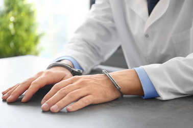 Doctor in handcuffs at workplace, closeup