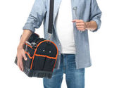 Photo Young plumber with tool bag and wrench on white background