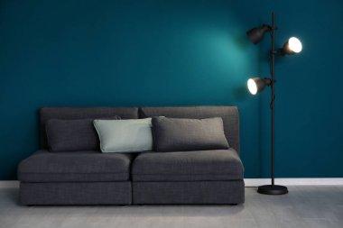 Elegant living room interior with comfortable sofa near wall
